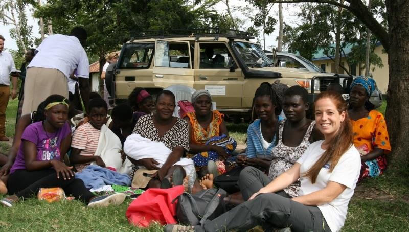 Cristina Sansalvador and Kenyan woman sitting on the grass at a mother-to-mother outreach, smiling into the camera.