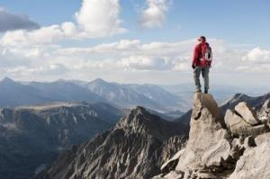 Hiker standing at the peak of a mountain""