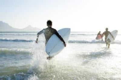 Young surfers running into the ocean with surf boards in their hands