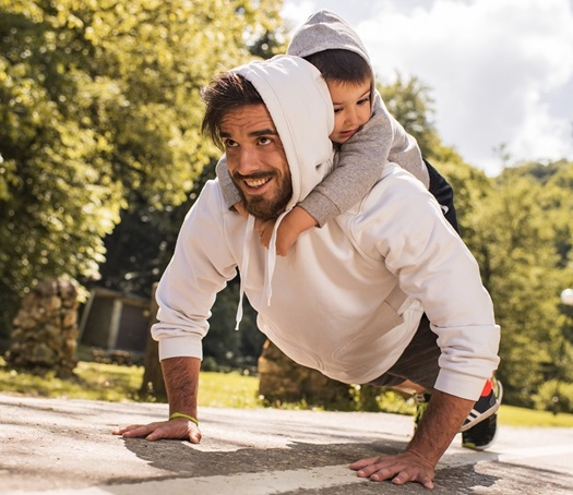 A young father exercising push-ups with his son on his back.