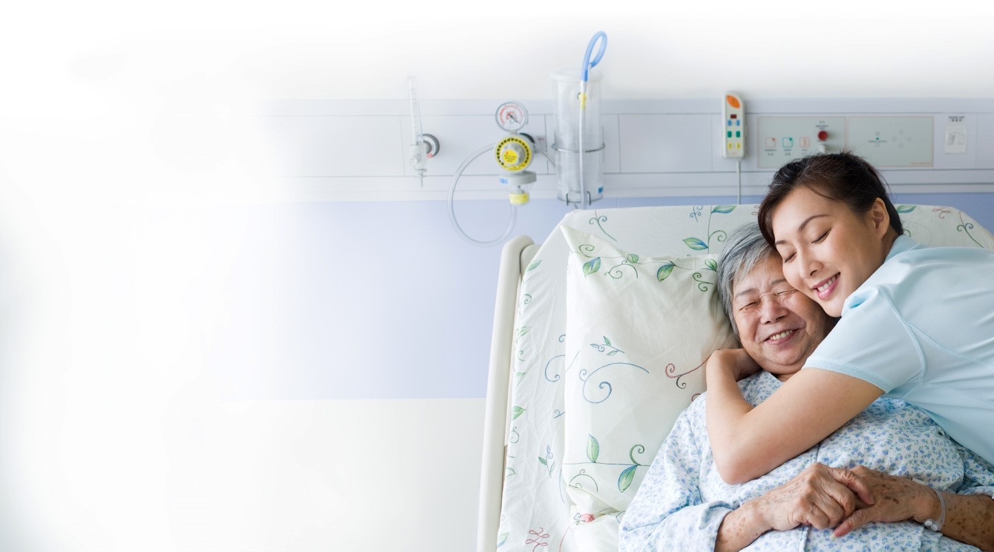 Nurse hugging a female patient, who is lying in her hospital bed – both are smiling