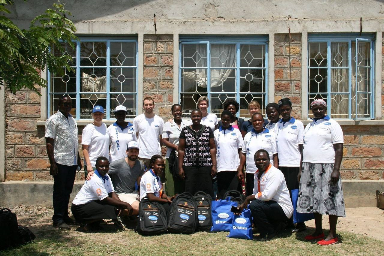 Members of the Kisumu community and HARTMANN volunteers standing in front of a building smiling into the camera.