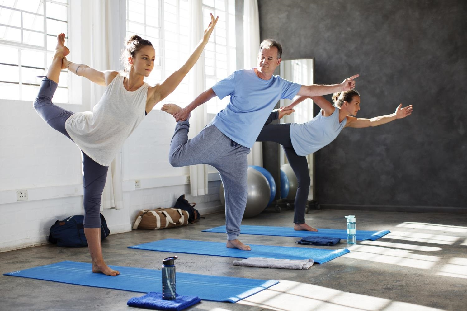 Man in a blue t-shirt trying to do yoga with two women