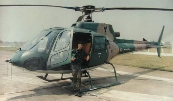 Marcos Dreher standing in front of a helicopter.