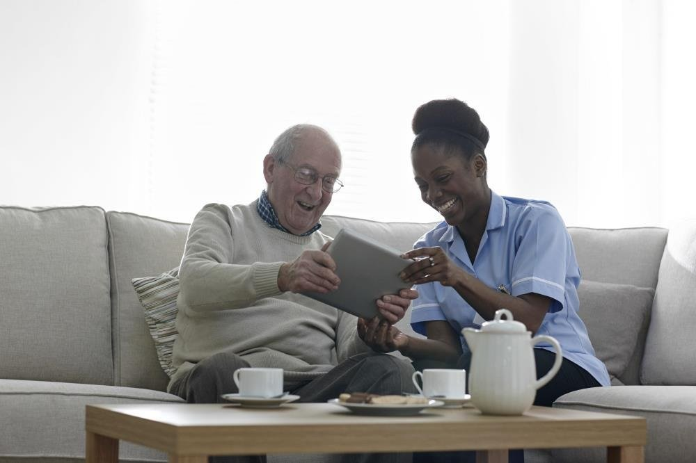 Female nurse and male patient sitting on the couch looking at a tablet and laughing