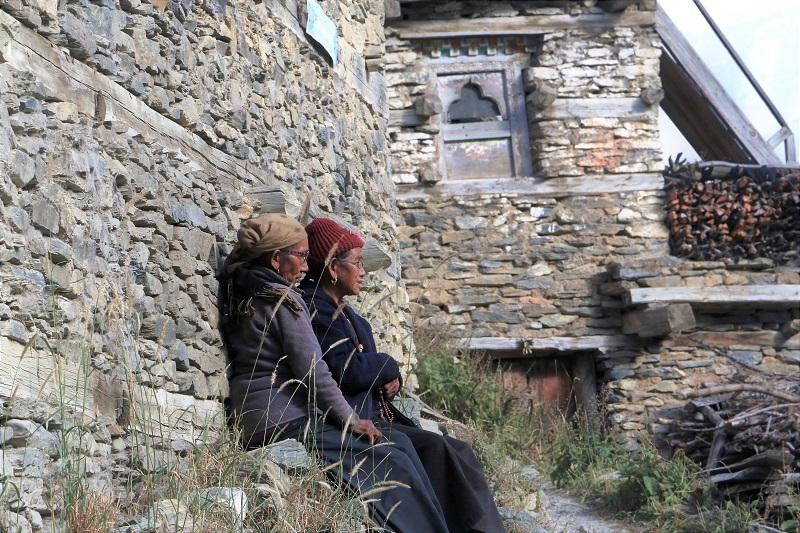 Nepalese women leaning against house wall.