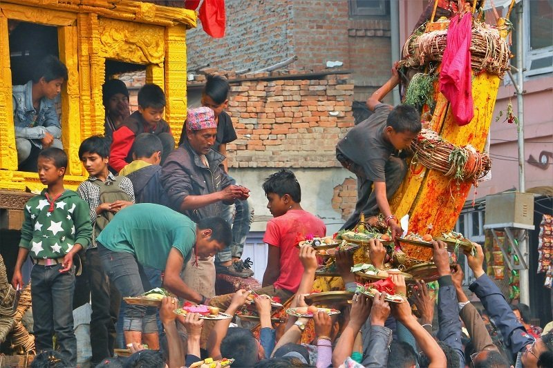 Nepalese people handing offerings up to a wagon.