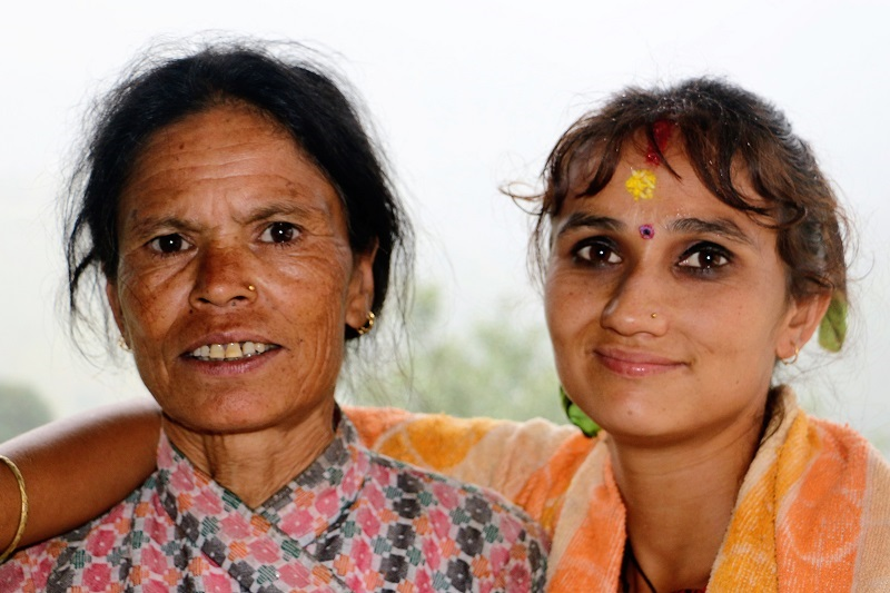 Two Nepalese woman smiling into the camera.