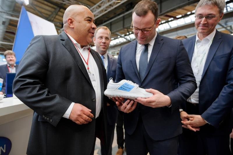 Chima Abuba handing over sport shoes to health minister Jens Spahn