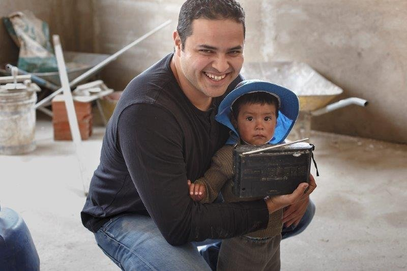 Fernando Sepulveda smiling into the camera with a Bolivian child