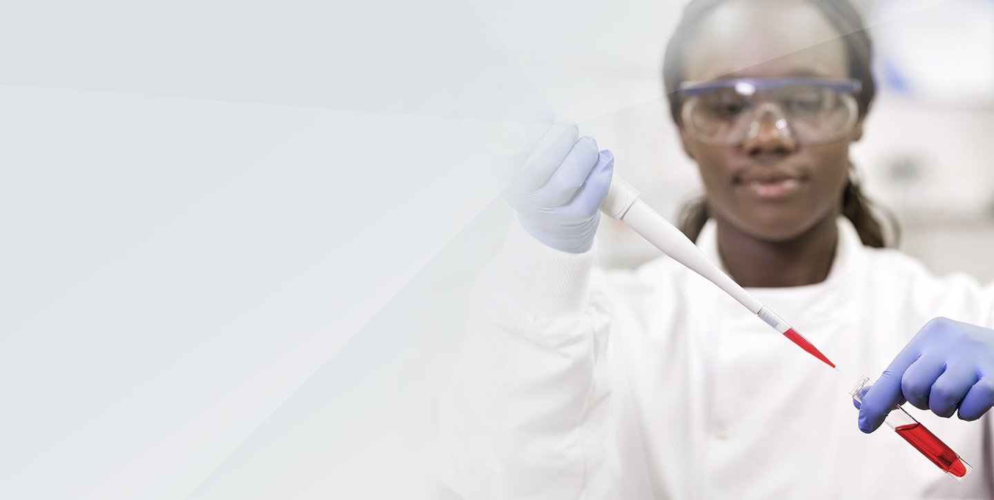 Female lab professional using pipette.