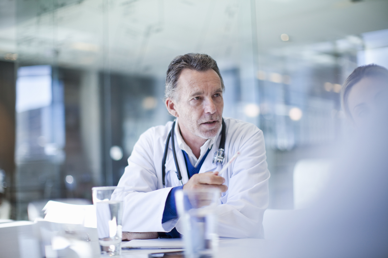 doctor sitting at a table, discussing with other people