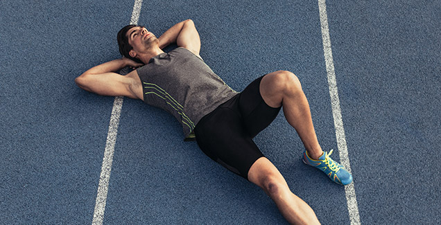 Man in sports dress laying on the ground.
