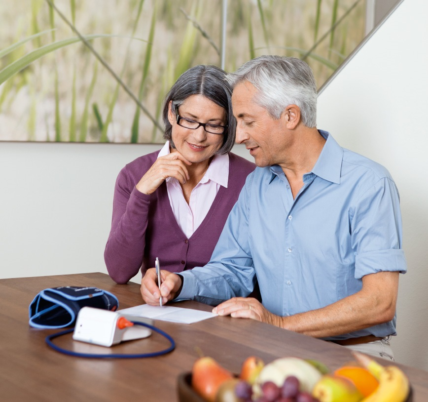 elderly couple sitting on a table with a blood pressure monitor writing something down