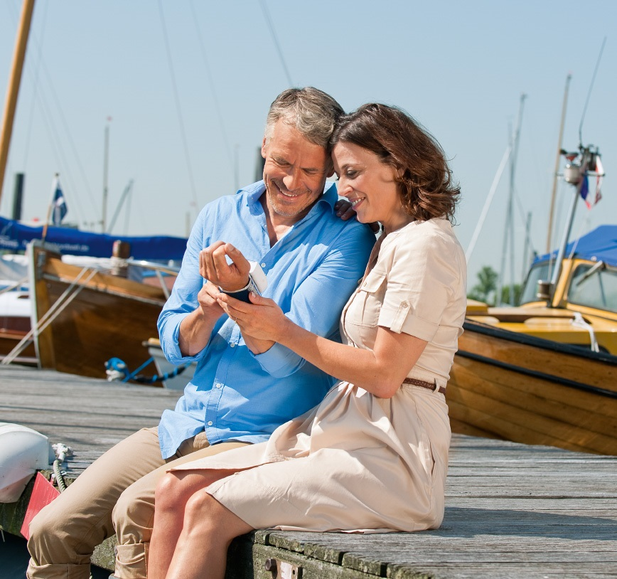 An elderly couple is sitting on a boat bridge, while the couple gaze the blood pressure meter at the husband's wrist.