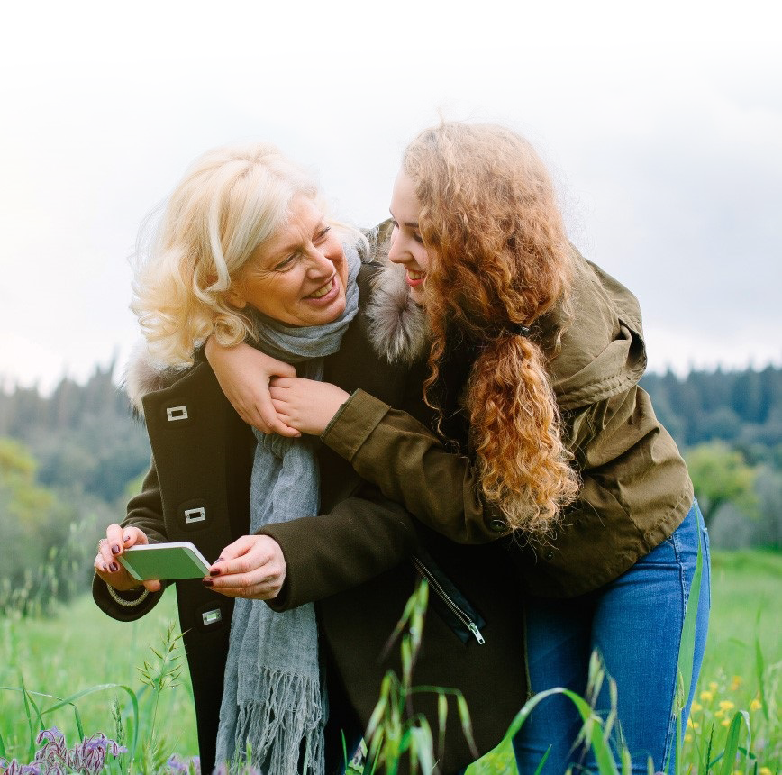 ersonal healthcare; grandmother and daughter hugging and smiling in a green field