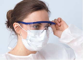 Woman wearing protective googles, a respirator mask and a protective gown
