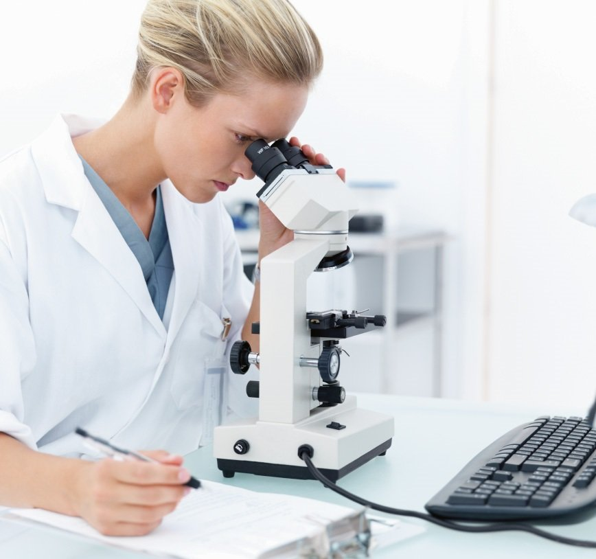 A woman, dressed in a surgery gown, is sitting in a lab, looking into a microscope