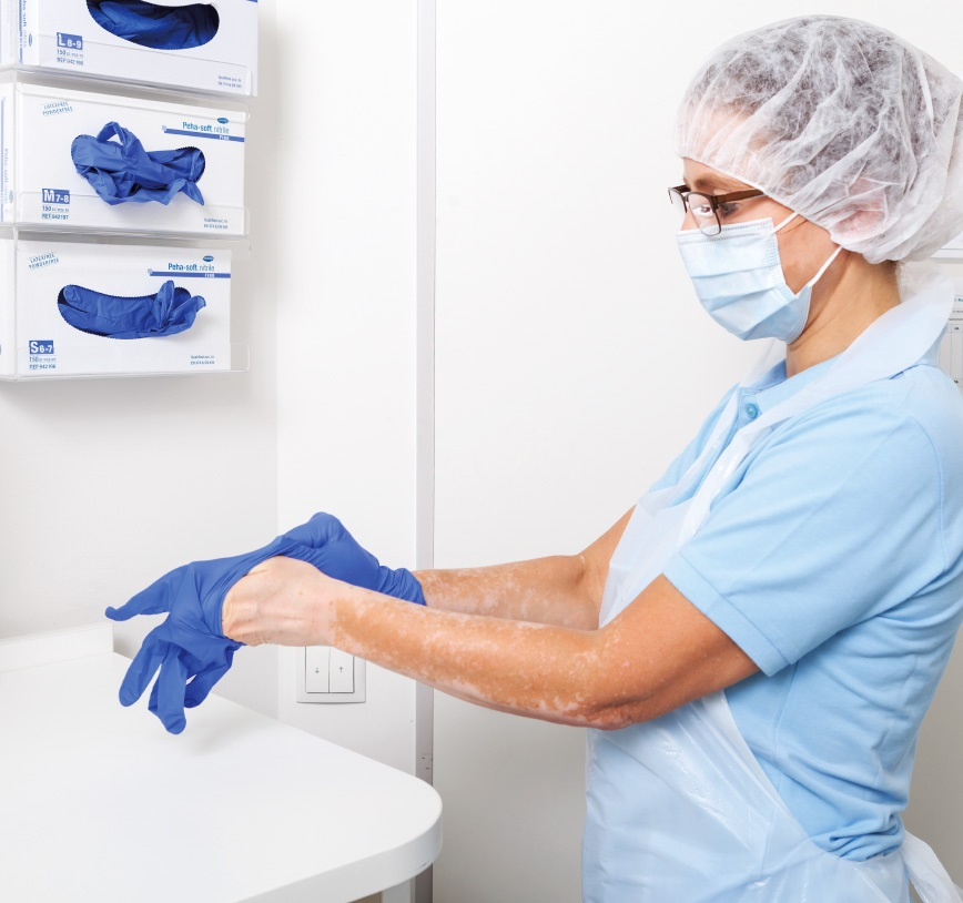 A nurse puts on gloves after disinfecting her hands.