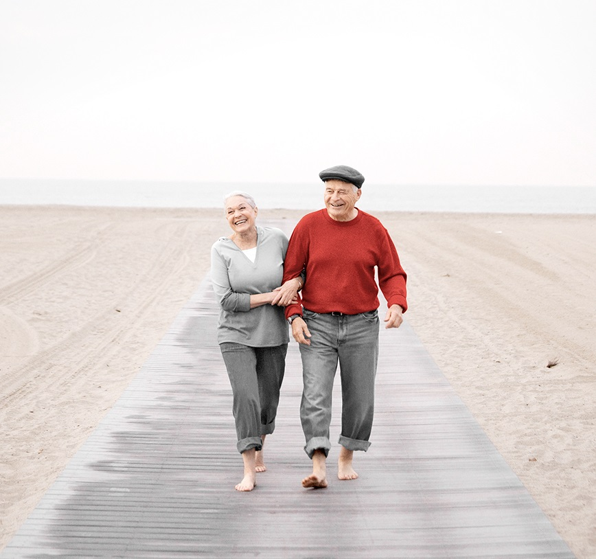 An elder couple is walking at the sea