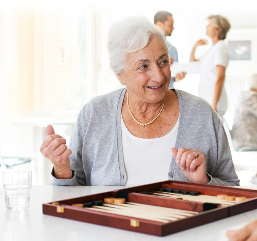 A happy-looking old lady is sitting at a table in a hospital room; in front of her is a board game. Two medical assistants standing far behind her and talking to each other.