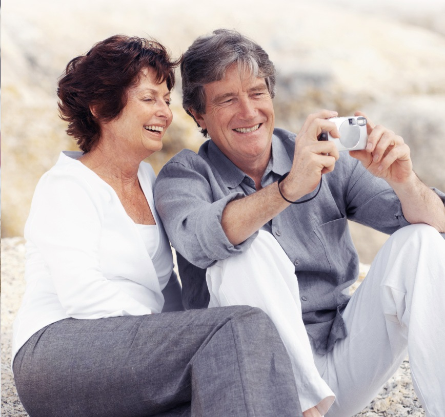 An elderly couple is sitting on rocky ground, while both of them are smiling into a camera, which the husband holds in front of them
