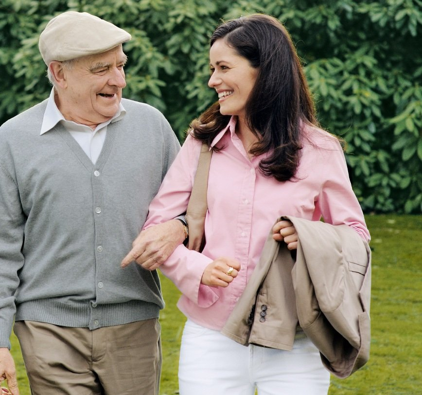 A young woman and an old man are walking together in a park.