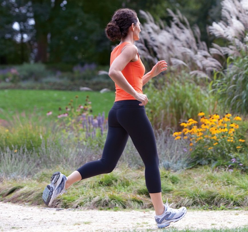 A woman, dressed in sport clothes, is jogging in a flourish park.