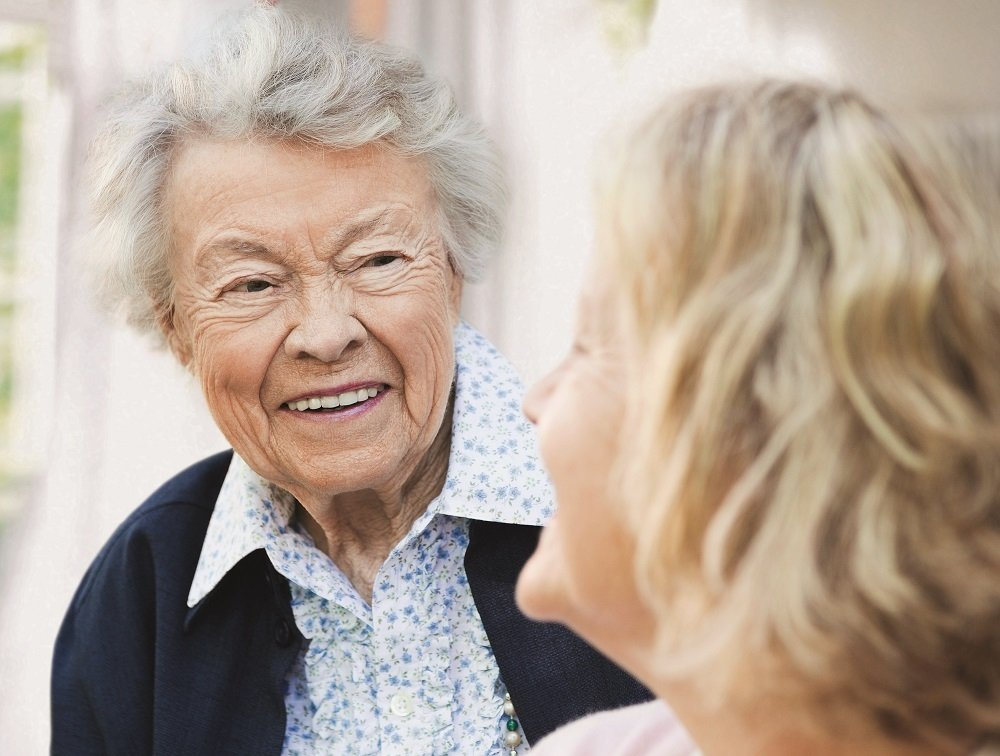 two old women talking with each other smiling