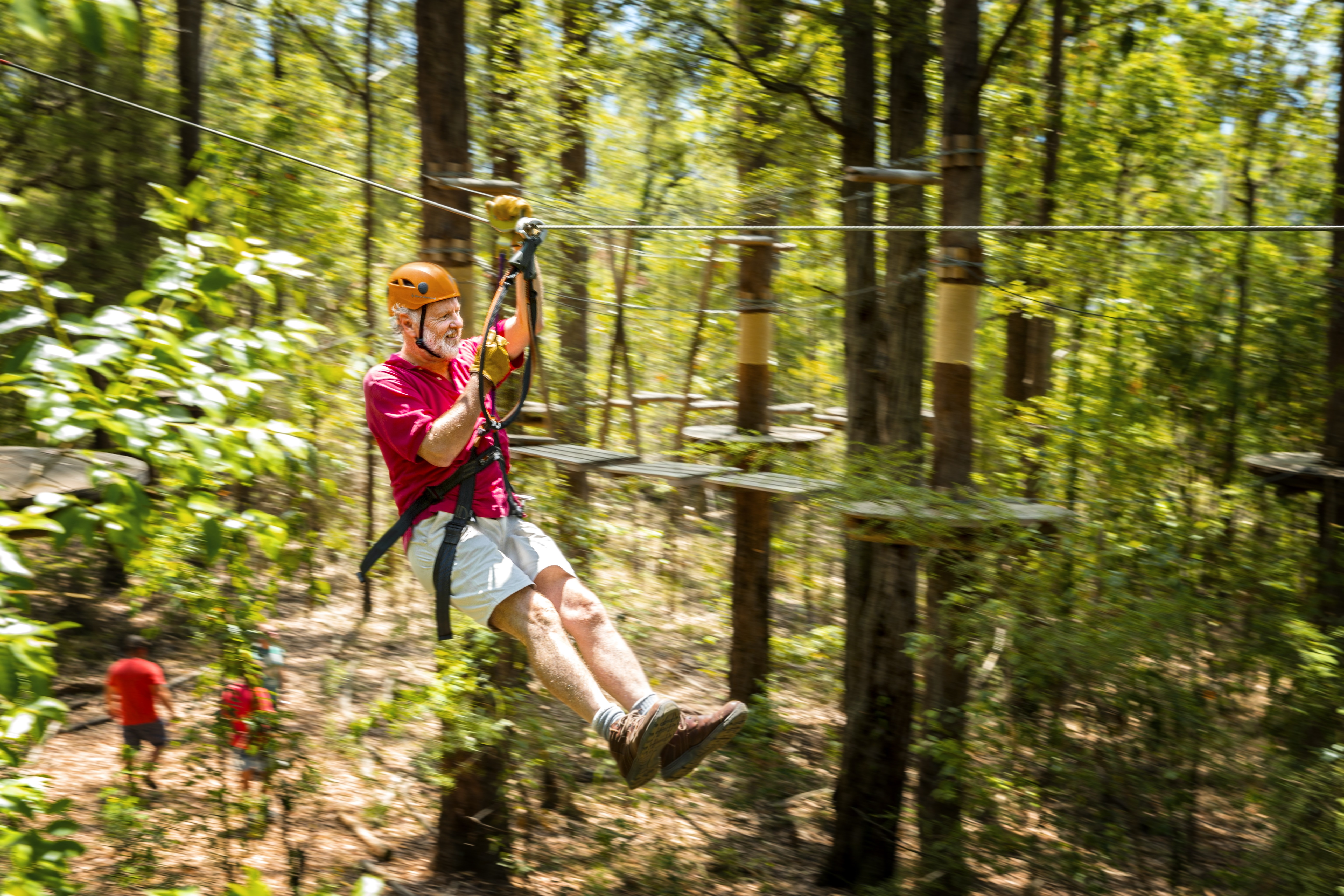 man with incontinence zip-lining in forest