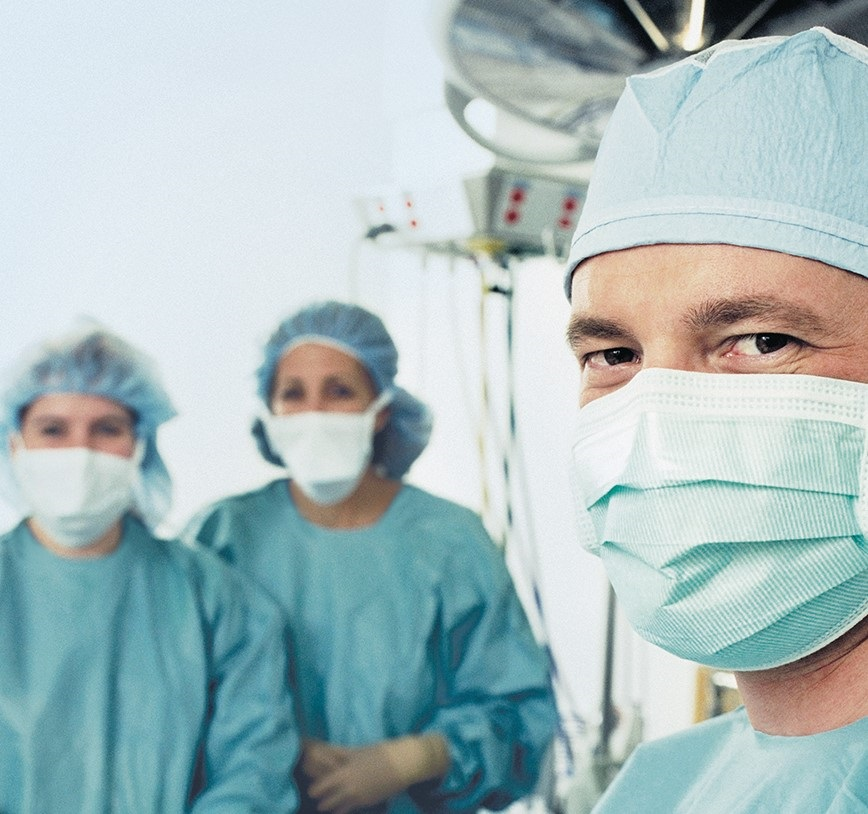 3 doctors, wearing surgical masks, are looking into the camera. Surgery equipment is shown in the background.