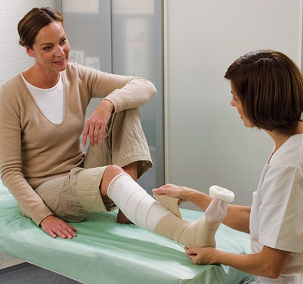 A nurse is treating the wound of a woman's foot