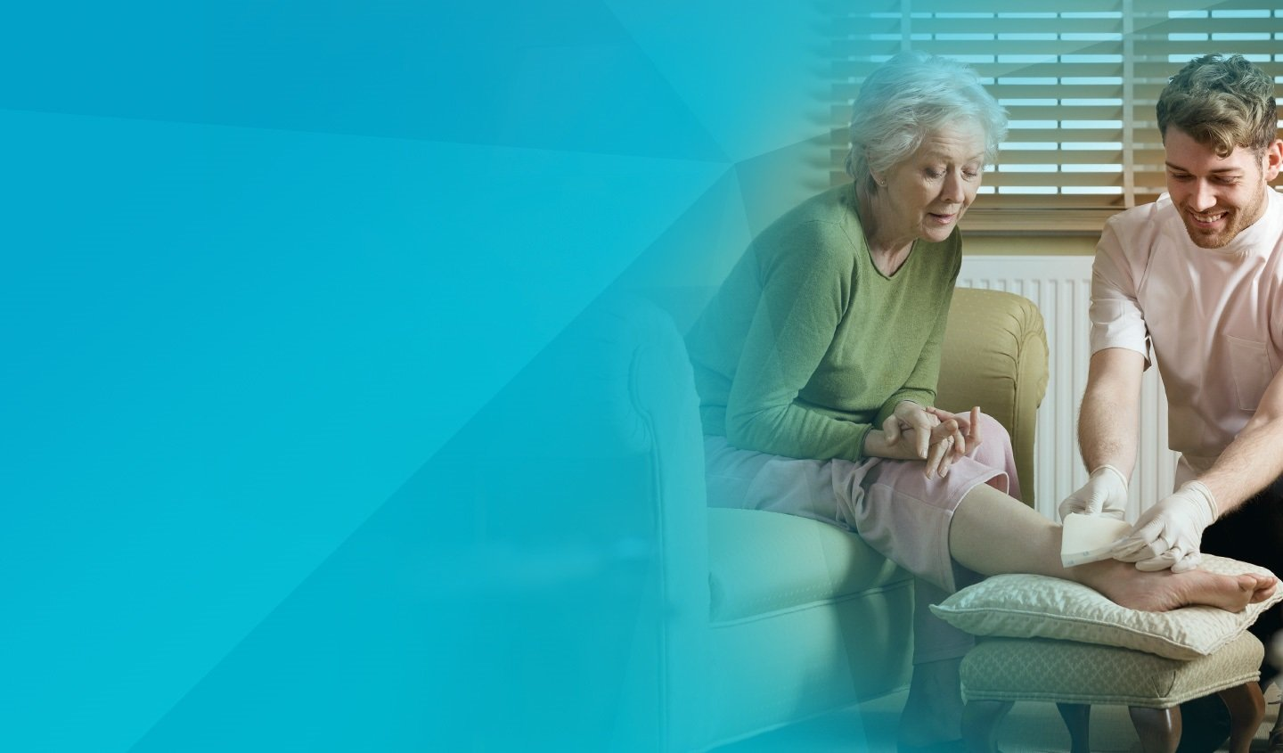 A care taker is bandaging a woman's leg