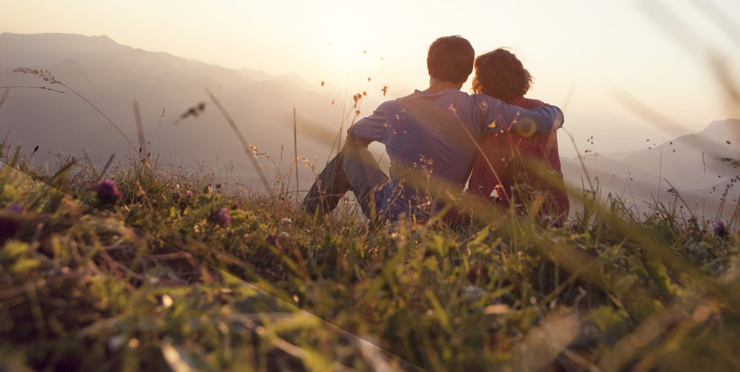 Couple sat on top of a mountain field full of long grass