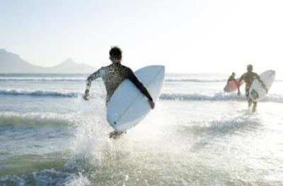 Young surfers running into the ocean with surf boards in their hands.