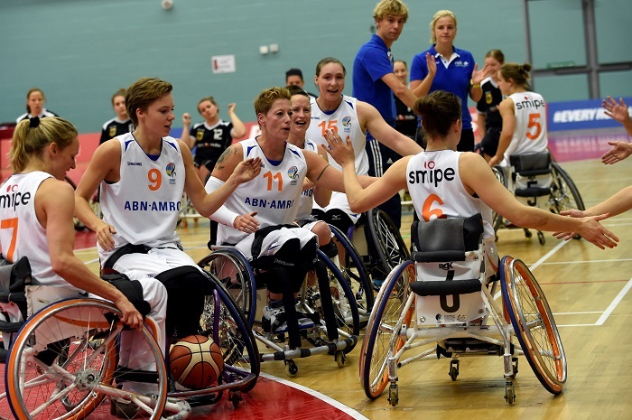 Picture of the women wheelchair basketball team on the field.
